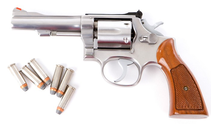 357 magnum revolver with several rounds of ammunition