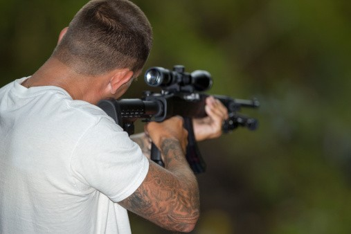 Rimfire shooter takes aim at targets in a forest.